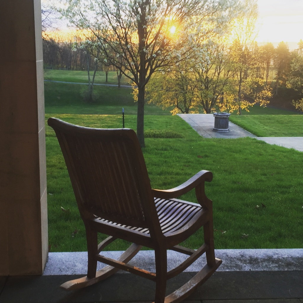 Photo of a rocking chair at sunrise.